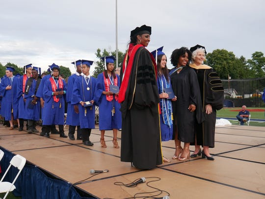 Poughkeepsie school board President Felicia Watson (left, standing) poses for photos with Poughkeepsie High School's newest graduates during the commencement ceremony on June 22, 2018. To the right are keynote speaker Quamisha Desroches (L) and Deputy Superintendent Kathleen Farrell.