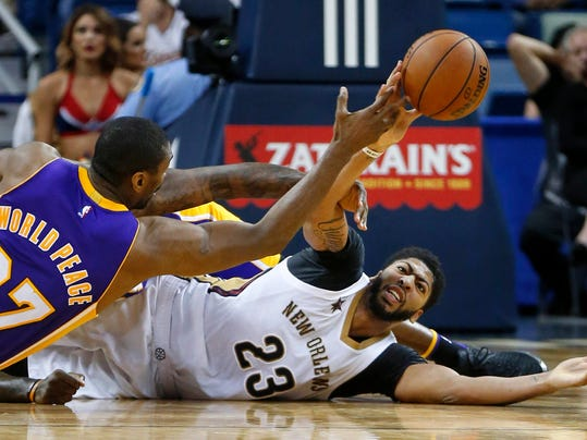 New Orleans Pelicans forward Anthony Davis (23) battles for a loose ball against Los Angeles Lakers forward Metta World Peace (37) in the second half of an NBA basketball game in New Orleans, Tuesday, Nov. 29, 2016. The Pelicans won 105-88. (AP Photo/Gerald Herbert)