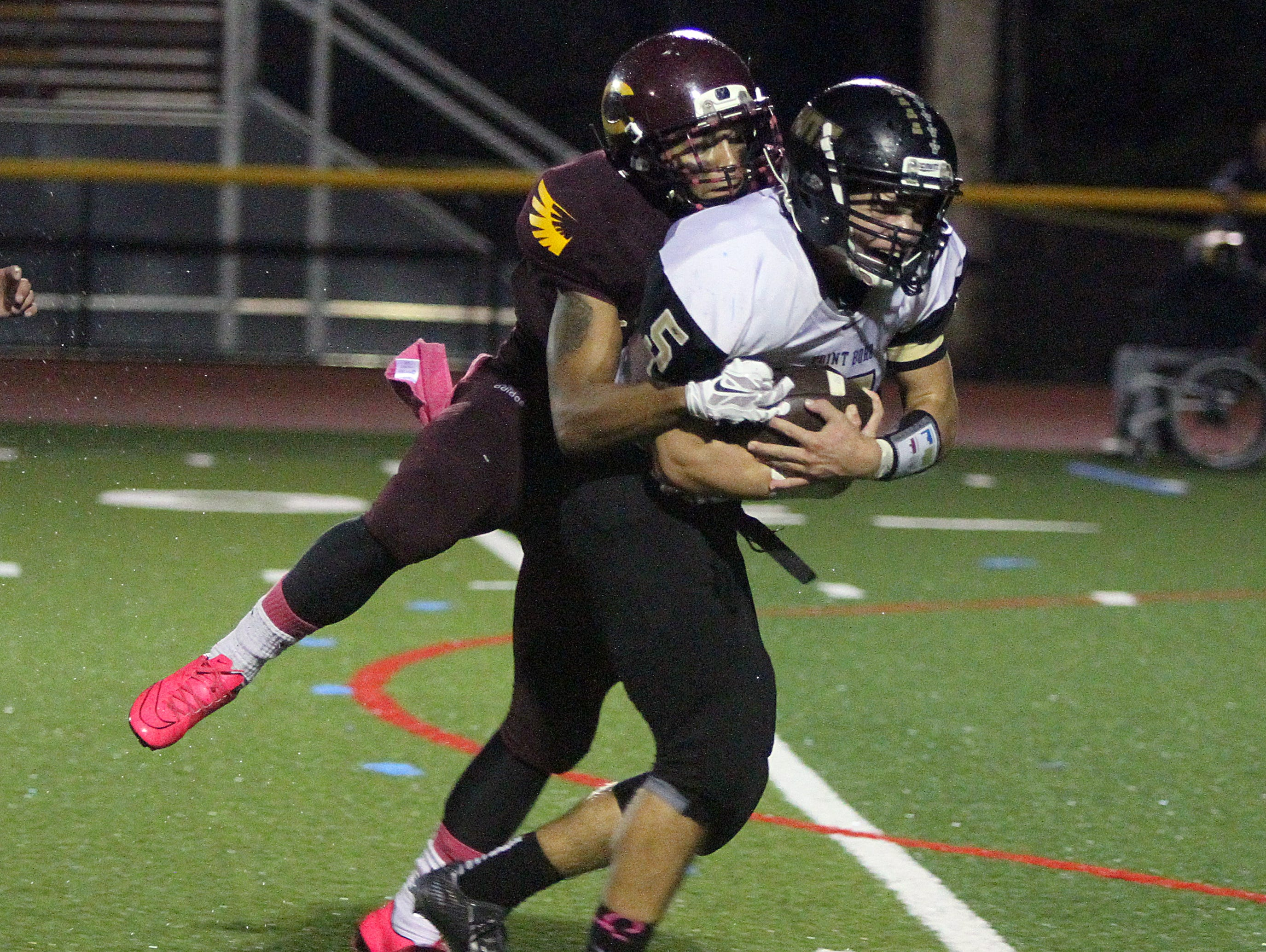 The Point Pleasant Boro Panthers traveled down the Garden State Parkway to take on the Central Regional Golden Eagles in a varsity high school football game on Friday October 9, 2015. Here Pt Pleasant Boro's # 5 (right) Nate Husak is tackled by Central Regional's # 5 (left)- Michael Miserendino.