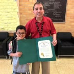 Scott Carl, principal at Loganville Springfield Elementary School, received a citation from the Baltimore County Executive's Office in honor of his retirement. He is shown with second-grader Cristiano Colón.