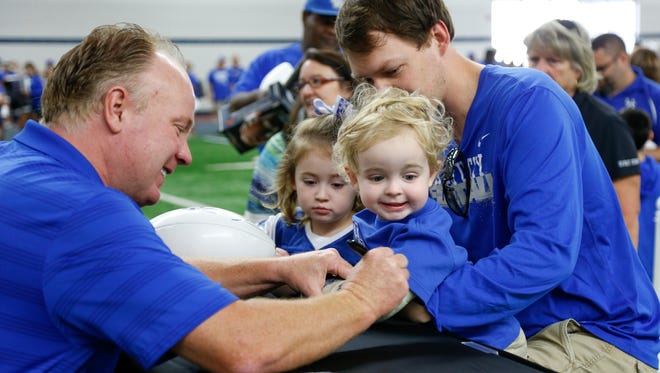 UK head coach Mark Stoops signs Samuel VanHoose, 2, of Lexington's cast during UK Football Fan Day in Lexington, Ky., on Saturday, August 5, 2017.