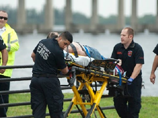 Police and EMS personnel take away a man they fished