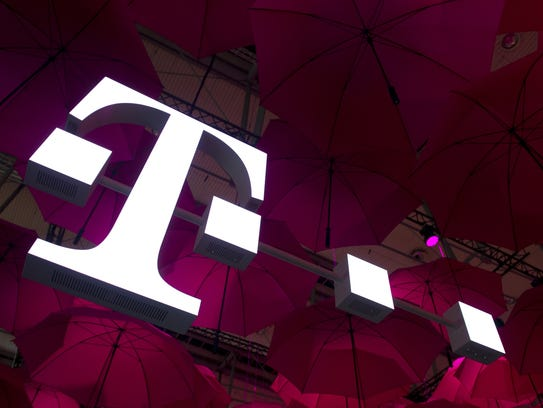 A T-Mobile logo hangs under pink umbrellas at the stand