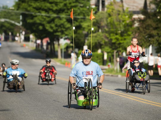 Handcyclists make their way up Pearl Street during the People's United Bank Vermont City Marathon on Sunday morning.