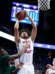 Scott County's Michael Moreno, 24, puts up two points against Trinity's Jamil Hardaway, left, during a first round game of the Whitaker Bank/KHSAA Boys' Sweet 16 basketball tournament played at Rupp Arena in Lexington, Ky. Wednesday March 14, 2018. (Photo by Gary Landers)