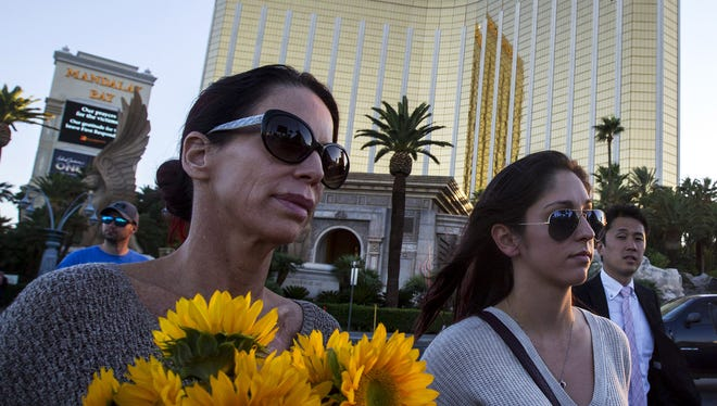 Christine Torres, left, and her daughter, Sydney Torres, carry flowers and a candle to a memorial for victims of the Las Vegas mass shooting on Tuesday, Oct. 3, 2017 in Las Vegas, Nev. Stephen Paddock was accused of shooting into a crowd of people at a concert from his hotel room at Mandalay Bay in Las Vegas on Sunday night, resulting in the deadliest mass shooting in U.S. history.