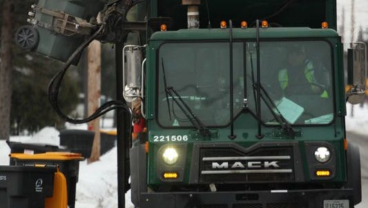 A truck with a mechanical arm from Advanced Disposal picks up a garbage container in Weston, Friday, February 6, 2015.