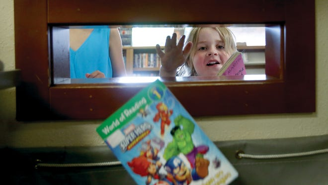 Ivan Churchman-Bailey, 4, of Bremerton drops a book into the drop box at the Kitsap Regional Library Sylvan Way branch in East Bremerton on July 10. The Kitsap Regional Library is getting rid of late fines as one of its levy promises.