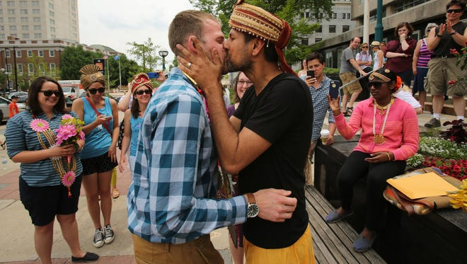 Todd Kinsman, 28, left, and Ravi Manghnani, 37, kiss after getting married outside the City-County Building the day after the ban on same-sex marriage was struck down in Wisconsin, in Madison, on Saturday. AP Todd Kinsman, 28, left, and Ravi Manghnani, 37, kiss after getting married by their friend, Michele Ritt, a Universal Life Minister, outside the City-County Building the day after the ban on same-sex marriage was struck down in Wisconsin, in Madison, Wis., Saturday, June 7, 2014. Kinsman and Manghnani, who have been together for seven years, had a ceremony a couple weeks ago and were just on their honeymoon in New York when they found out the ban was lifted and flew back home Saturday morning to get married in Madison.