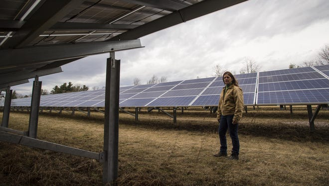 Meg Armstrong Whitcomb, a consulting engineer, stands among solar panels Thursday at her family's farm in Essex Junction.