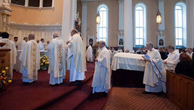 Priests file by Bishop Emeritus Kenneth Angell's casket during funeral services at St. Joseph's Co-Cathedral in Burlington on Tuesday, October 11, 2016.