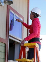 San Juan College building trades program student Jenny Lee cleans a window on one of the new houses featured in a program open house planned for Saturday.