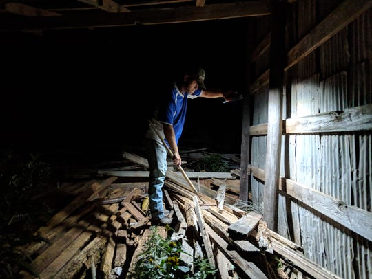Richard Luna searches through the ruins of an old barn