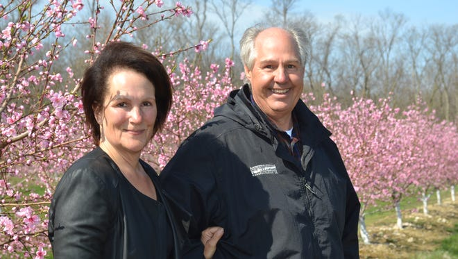 Donna and Quintin Smith stand amidst the blossoming peach trees in their Catawba Island orchard. They are seeking support for the construction of a microbrewery on the farm that will utilize stone fruit in the recipes.
