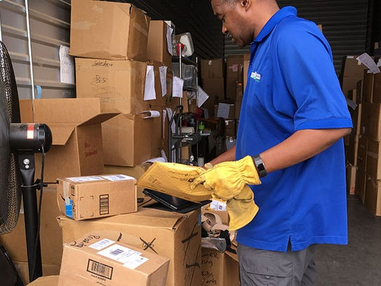 Johnny Mitchell Jr., of the Bra Recyclers, scans the