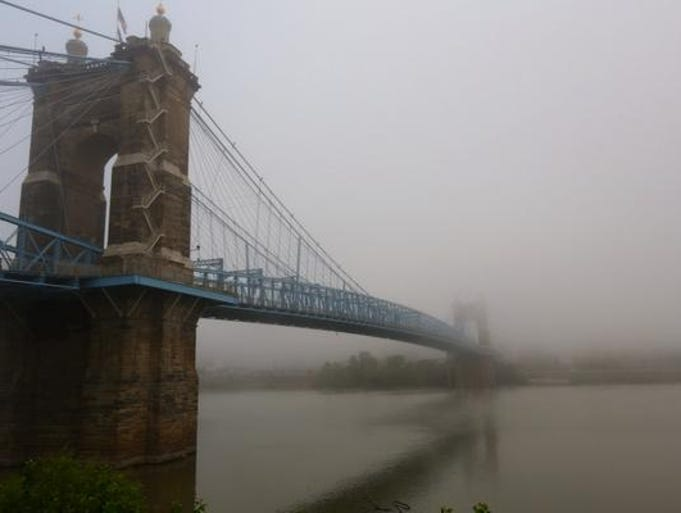 Fog is heavy near the Roebling Suspension Bridge from the Covington waterfront.