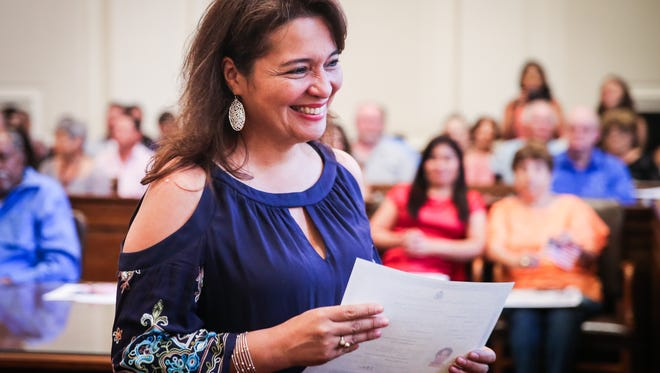Maria Elvira Avellaneda Rubio walks back with her certificate during the naturalization ceremony Wednesday, June 6, 2018, at O.C. Fisher Federal Building.