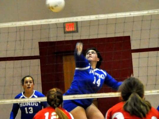 Hondo's Gennisis Gutierrez leaps to hit the ball over