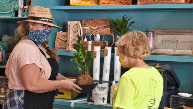 Runaway Luna Coffee House & Lifestyle Boutique owner Cathy Galbraith, left, discusses a plant with a customer last week. The store's Instagram account and Galbraith's personal Facebook account were hacked in mid-July, Galbraith said.