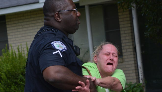 Connie LeBlanc, mother of Christopher LeBlanc, is held by a Pineville Police officer Monday morning at the scene of her son's shooting death on Cummins Street. Christopher LeBlanc allegedly charged  officers with a weapon as they arrived to investigate a disturbance call, according to a Pineville Police release.