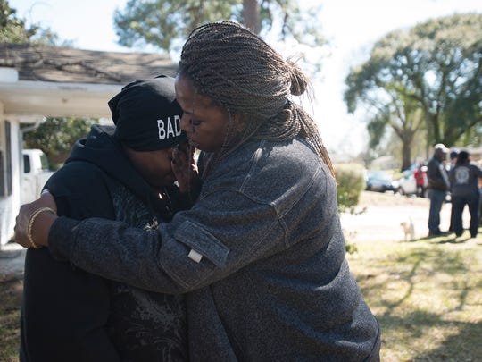 Kimberly Gunn, sister of Greg Gunn, left, is embraced by family friend Pam Blocton while mourning the police involved shooting death of her brother Greg Gunn on the property where he was shot at 3237 McElvy Street in Montgomery, Ala., on Thursday, Feb. 25 2016. Gunn was shot by a Montgomery Police Officer earlier that morning.