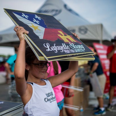 """Meredith Cantrelle, 8, holds a handful of """"Lafayette Strong"""" signs while volunteering at a distribution event at Cajun Field in Lafayette, La., Wednesday, July 29, 2015. Pixus Digital Printing created and is selling a design based on the """"Lafayette Strong"""" theme to raise funds for the victims of the Grand Theatre shooting."""
