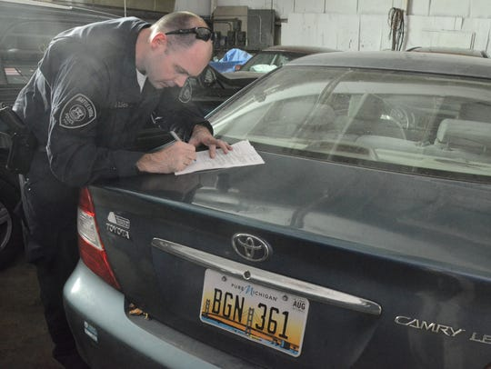Battle Creek Officer Andrew Olsen completes the paperwork