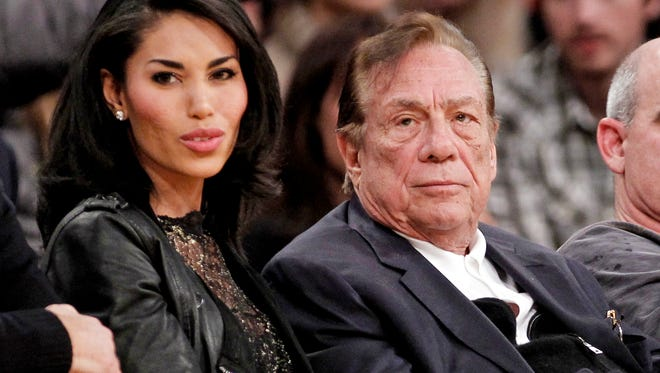 FILE - In this Dec. 19, 2011, file photo, Los Angeles Clippers owner Donald Sterling, right, sits with V. Stiviano as they watch the Clippers play the Los Angeles Lakers during an NBA preseason basketball game in Los Angeles. A Los Angeles judge ruled Tuiesday April 14, 2015 that the wife of the former Clippers owner is owed $2.6 million by V. Stiviano, a woman Donald Sterling showered with gifts. (AP Photo/Danny Moloshok, File)