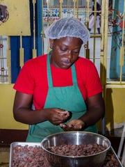 Vivaldie Gustave sorts cacao beans for Askanya, Haiti's