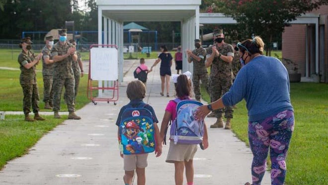 Marines from the 10th Marine Regiment recently welcomed students back to school at Johnson Primary School aboard Camp Lejeune. Previously the Marines helped clean up the campus, build sneeze guards and constructed an outdoor classroom for the students return.