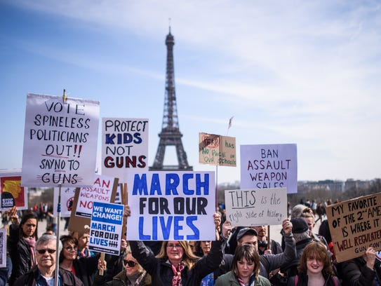 French and Americans hold anti-gun posters as they