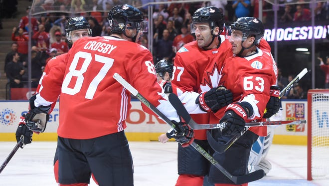 Team Canada's Brad Marchand (63) celebrates with teammates Patrice Bergeron (37) and Sidney Crosby (87) after scoring a goal against Team Europe.