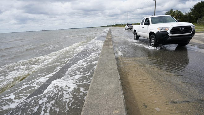 Waters from the Guld of Mexico poUr onto a local road, Monday, Sept. 14, 2020, in Waveland, Miss. Hurricane Sally, one of a record-tying five storms churning simultaneously in the Atlantic, closed in on the Gulf Coast on Monday with rapidly strengthening winds of at least 100 mph (161 kph) and the potential for up to 2 feet (0.6 meters) of rain that could bring severe flooding.