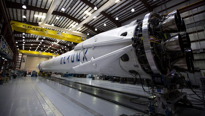 SpaceX Falcon 9 rocket and Dragon capsule shown April 2, 2015, undergoing preparations in Florida for a planned Monday, April 13, 2015, launch of cargo to the International Space Station.