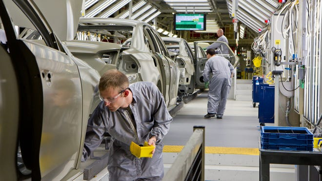 Paint shop workers attend to Volkswagen Passat sedans at the German automaker's plant in Chattanooga, Tenn., on Tuesday, July 31, 2012. (AP Photo/Erik Schelzig)