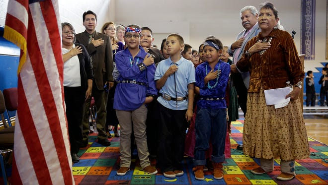 In this Sept. 26, 2014, photo, students and faculty say the Pledge of Allegiance during an assembly at the Crystal Boarding School in Crystal, N.M. on the Navajo Nation. The school is one of 183 for Native American students run by the Interior Department's Bureau of Indian Education. Interior Secretary Sally Jewell on Wednesday, Nov. 2, 2016, named Tony Dearman, who is Cherokee, to head the Bureau of Indian Education, a division of the U.S. Interior Department that has oversight of nearly 200 schools in some 20 states.