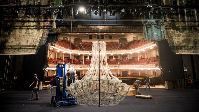 The Cincinnati Opera stage crew assembles a chandelier for La Traviata, an opera by Giuseppe Verdi, at Music Hall Monday, June 4, 2018. The chandelier is adorned with plastic and spoons.