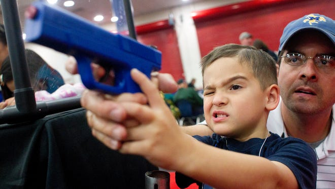 Heath Bryant of Cypress, Texas, assists his son, Tate, 5, to shoot a target using a video game-style of gun at an exhibit booth  during Youth Day events at the National Rifle Association's 2013 convention in Houston.