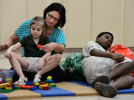 Special education teacher Miranda Good teaches Kyrato put together toy blocks during summer school Monday in Murfreesboro. Good earned her degree May 6 from Western Governors University Tennessee.