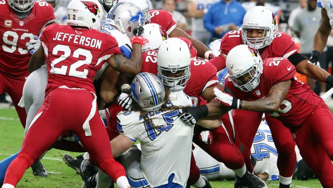Arizona Cardinals defense players swarms Detroit Lions fullback Jed Collins (C, bottom) during their NFL game in Glendale, Arizona, USA, 16 November 2014. The Cardinals won 14-6 to give them a 9-1 record on the season.