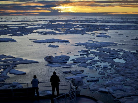 Researchers look out from the Finnish icebreaker MSV Nordica as the sun sets over sea ice in the Victoria Strait along the Northwest Passage in the Canadian Arctic Archipelago. Studies show the Arctic is heating up twice as fast as the rest of the planet.