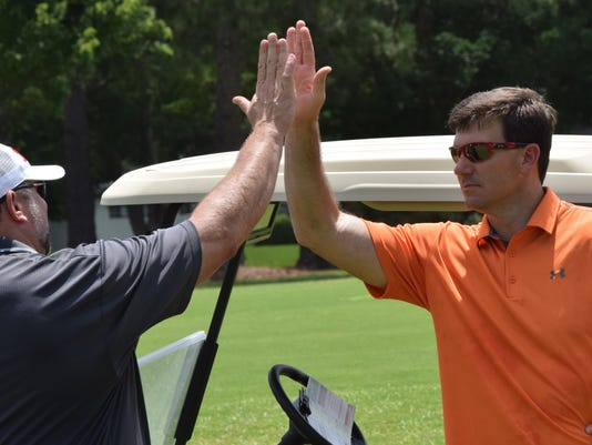 ANI Oak Wing Golf Jake Delhomme (right) high-fives Buck Moncla on the course at Oak Wing Golf Club Friday, June 26, 2015.-Melinda Martinez/The Town Talk