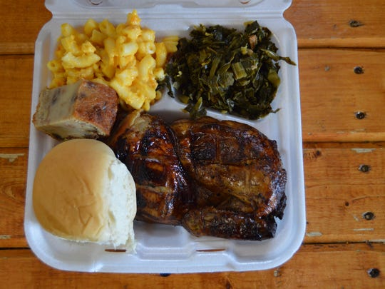 A barbecue chicken platter from EM-INGS, with homemade mac and cheese, collard greens and a roll.