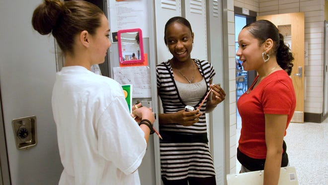 Students chat at their lockers during class break.