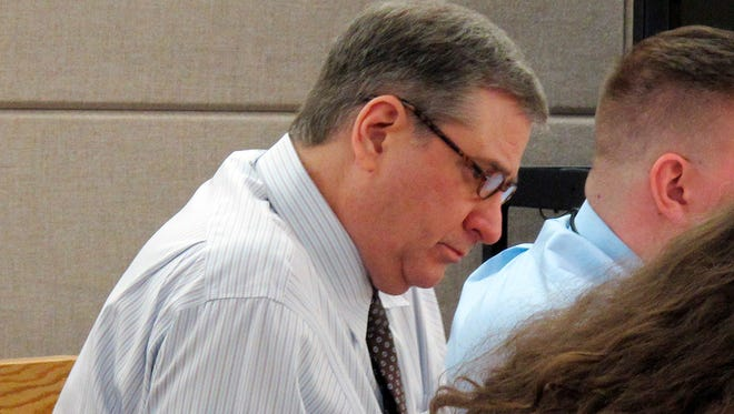 Mark Desimone, a former Arizona legislator charged with killing a man on an Alaska hunting and fishing trip in 2016, looks over documents during his trial in Juneau, Alaska, on May 10, 2018.