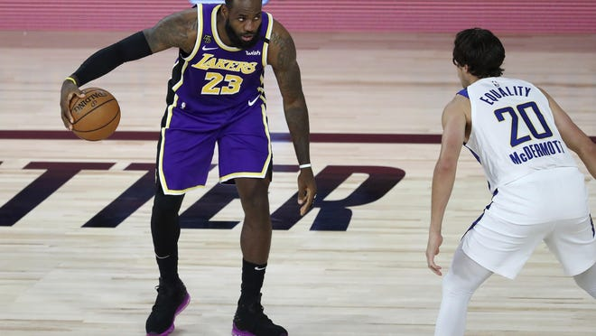 Los Angeles Lakers forward LeBron James handles the ball against Indiana Pacers forward Doug McDermott during the first quarter Saturday, Aug. 8, 2020, in Lake Buena Vista, Florida.