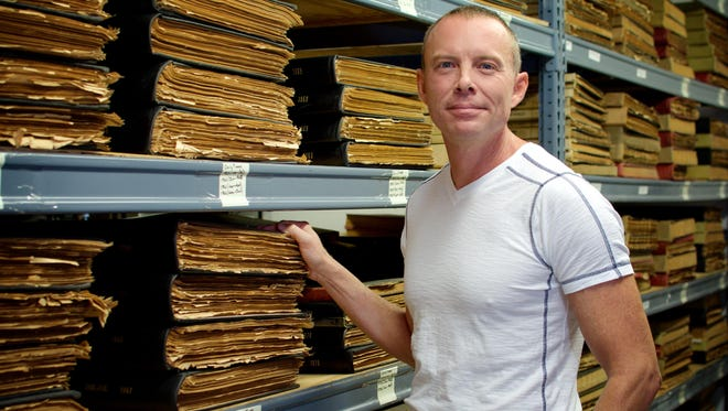 Michael Boonstra is genealogy librarian at the Central Brevard Library in Cocoa. Here he shows old newspapers in the Brevard Historical Commission archives.
