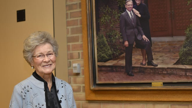 Ruth Merillat is pictured in November 2013 at the Christian Family Centre in Adrian, next to a portrait of herself and her late husband, Orville. Merillat, who with Orville co-founded The Centre, Lenawee Christian School and their cabinetry business, Merillat Industries, died Wednesday at the age of 99.