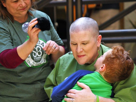 Ruidoso Shave for the Brave organizer Natalie Davis hugs her grandson Cevy while Bare Essential employee Rhonda Newsome brushes off Davis' head during Saturday's fundraiser.