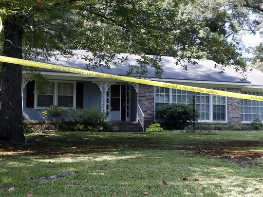 Police crime scene tape surrounds the residence of